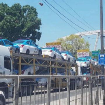 Caminhão cegonha com carros da PM fica preso embaixo da linha férrea no Centro