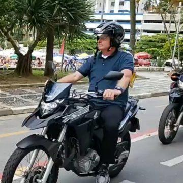 Bolsonaro comete infração de trânsito ao andar de moto com capacete solto em Guarujá